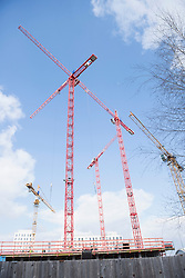 Low angle view of cranes at construction site cloudy sky, Munich, Bavaria, Germany