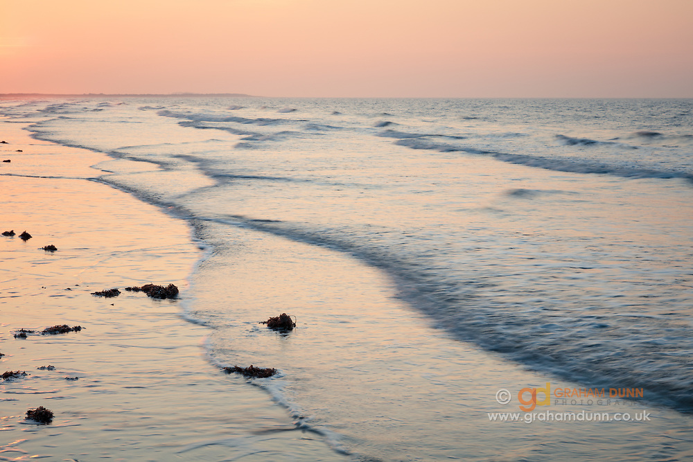 Wonderful sunset hues of orange and pink reflect in calm waters on Brancaster Beach. A colourful dusk scene in North Norfolk, East Anglia, England, UK.