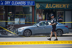 Police are investigate a car with a bullet hole within the scene of a shooting in east Toronto, on Monday, July 23, 2018. Police were trying Monday to determine what prompted a 29-year-old man to go on a shooting rampage in a popular Toronto neighbourhood, killing two people and injuring 12 others. THE CANADIAN PRESS/Christopher Katsarov