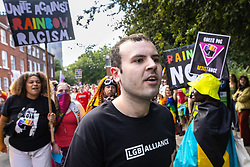 """© Licensed to London News Pictures . 28/08/2021. Manchester, UK. A man wearing an anti-trans LGB Alliance t-shirt stands amongst demonstrators at the pro-trans-rights demo. People take part in a Reclaim Pride march through Manchester City Centre , in opposition to the management of the city's """"official"""" Manchester Pride charity festival . The Manchester Pride charity parade was cancelled in 2020 due to Coronavirus . An """"equality march"""" organised by Manchester Pride charity was due to take place on Deansgate as the protest passed through the Gay Village . Protesters object to Manchester Pride charity's withdrawal of funding for the LGBT Foundation's condom distribution scheme and HIV charity George House Trust as well as increasing commercialisation of the annual event . Photo credit: Joel Goodman/LNP"""