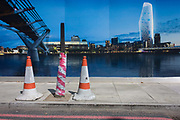Cones and a hoarding showing the Thames River, Millennium Bridge and Tate Modern. We see a visual pun between the cones and severed stripe-wrapped tree that blends together with the tower of the Tate - a former electricity generating power station. The future skyscraper is 1 Blackfriars or One Blackfriars, a mixed-use development approved for construction at the junction of Blackfriars Road and Stamford Street at Bankside, London. The development make make up a 52-storey tower of a maximum height of 170m and two smaller buildings of 6 and 4 stories respectively. Uses include residential flats, a hotel and retail. In addition a new public space will be created.