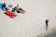 Nederland, Nijmegen, 1-8-2020 Een warme dag in de zomer . Mensen trekken naar de oevers van de waal en de spiegelwaal in het rivierpark aan de overkant van Nijmegen . De warmte, hoge temperatuur, drijft mensen naar het water . Het is verboden in de rivier te zwemmen vanwege de stroming en het drukke scheepvaartverkeer . . Vanwege de coronadreiging moet afstand gehouden worden, maar vooral jongeren, jonge mensen, zitten soms in groepen bij elkaar . Een jonge vrouw, meisje,  loopt met haar puppie in de armen langs een groepje jongens .Foto: ANP/ Hollandse Hoogte/ Flip Franssen