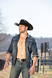hot masculine cowboy with an open shirt on a ranch