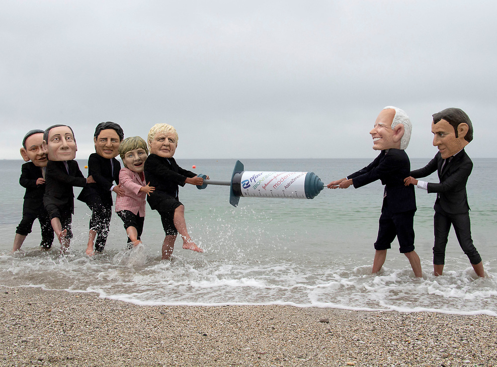 Members of the People's Vaccine group dress up as G7 leaders and splash each other in the sea at Swanpool, Cornwall. The costumed protesters also hold a big vaccine needles between them. 11th June 2021. Anna Hatfield/Pathos