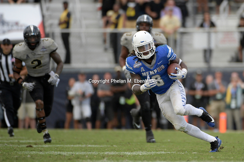 Memphis running back Darrell Henderson (8) rushes for yardage Central Florida linebacker Chequan Burkett (2) follows during the second half of the American Athletic Conference championship NCAA college football game Saturday, Dec. 2, 2017, in Orlando, Fla. Central Florida won 62-55. (Photo by Phelan M. Ebenhack)