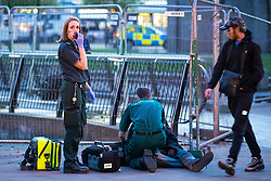 © Licensed to London News Pictures . 07/04/2017 . Manchester , UK . Paramedics helping a man , lying collapsed on the pavement on Piccadilly Gardens . Greater Manchester Police have authorised dispersal powers and say they will ban people from the city centre for 48 hours , this evening (7th April 2017) , in order to tackle alcohol and spice abuse . Photo credit : Joel Goodman/LNP