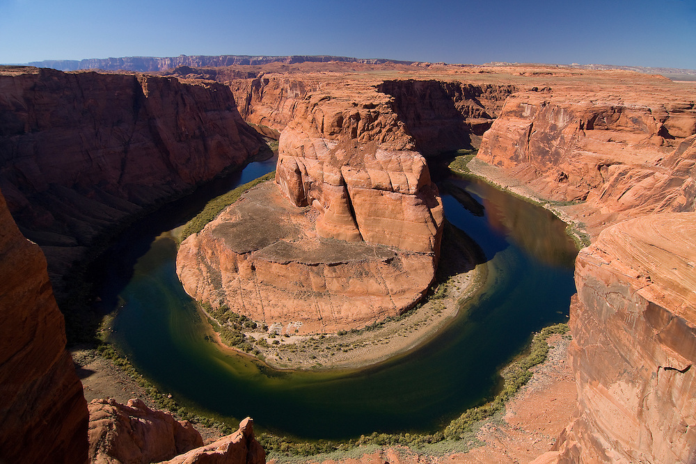 Horseshoe Bend is the name for a horseshoe-shaped bend of the Colorado River. It is located slightly downstream from the Glen Canyon Dam and Lake Powell within Glen Canyon National Recreation Area, about four miles south of Page, AZ. It can be viewed from the steep cliff above, forming a spectacular vista.