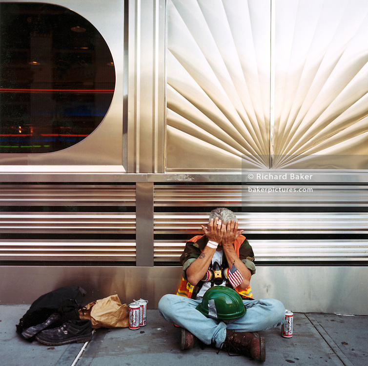 Ground Zero volunteer, Manhattan. Patriotic Americana - After 9/11. Ground Zero volunteer sits on a mid-town sidewalk (pavement). In the week after the September 11th attacks, America sought to express their anger and patriotic unity..