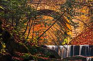 Cascade of waterfalls under a stone bridge in an autumn forest