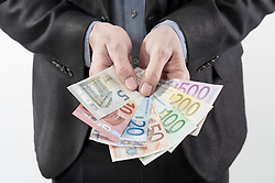Mid section view of businessman showing euro banknotes, Bavaria, Germany
