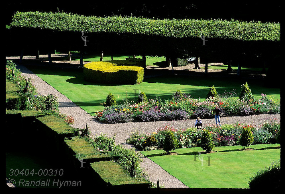 View of two visitors enjoying colorful flora inside Italian Garden, as seen from roof of Glamis Castle; Glamis, Scotland.