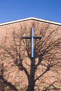 The cross on the wall of Herne Hill's United Reform Church and shadow of bare winter tree.