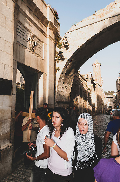 Jerusalem - October 19, 2010: Christian pilgrims carry a cross out the entrance to the Monastery of the Flagellation, located on the Via Dolorosa. It is here, according to tradition, that Pontius Pilate sentenced Jesus to death by crucifixion, and where he was flogged and forced to carry the cross.