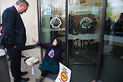 Three activists super glued themselves to the glass doors of the Shell Building and two scaled the glass awning in protest against the oil companys continued exploitation of fossil fuels, 15th April 2019, Central London, United Kingdom. Katarina Hasapopoulos discusses with a Shell emplyee. A number of arrests were made. The environmental protest group Extinction Rebellion has called for civil disobedience and peaceful protest to force the British government to take drastic action on climate change. The group wants the governenmet to tell the truth and admit that the impact of climate change is much more severe than they say and that action to mitigate catastrophic climate change is urgent.