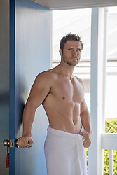 muscular man in a towel by a doorway