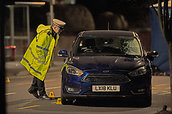 © Licensed to London News Pictures. 14/01/2019. Anerley, UK. Police officer looking at a blue car which has a smashed windscreen. A mother has been killed and a child is in hosptial fighting for life after being hit by a car crossing the road in Anerley near Penge.<br />   Photo credit: Grant Falvey/LNP