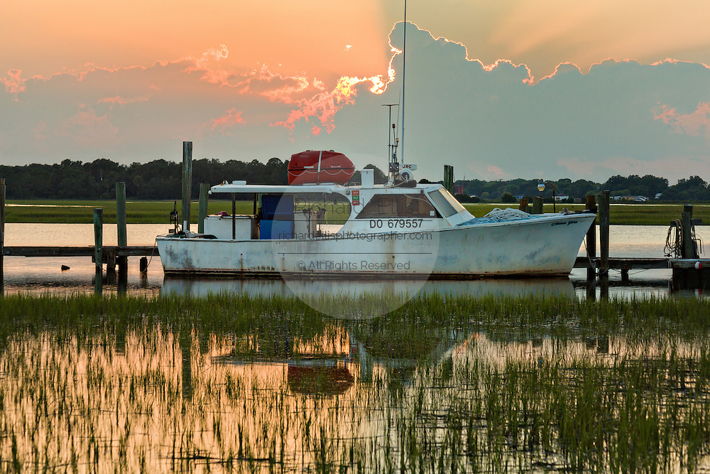 A crab boat tied up to the Crosby dock at sunset in Folly Beach, SC.