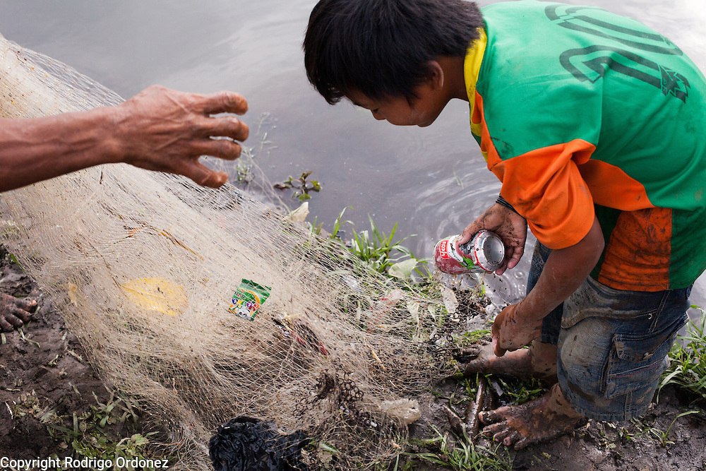 A man and a boy examine their catch on the bank of the Citarum river near Cikarees, Bale Endah district, Bandung regency, Indonesia. The net contains soda cans, plastic bags and other types of waste. ..The Citarum river, which runs about 270 kilometers through the province of West Java, is considered to be among the world's dirtiest. Over the last twenty years, the river has been severely polluted by toxic industrial waste, trash and raw sewage. The Citarum is one of the main sources of freshwater for West Java and supplies about 80% of water for Indonesia's capital Jakarta.