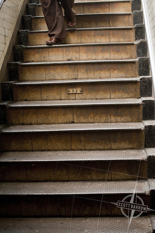 Legs climbing subway stairs in New York City.