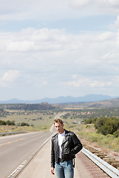 man in a leather jacket on a road in New Mexico