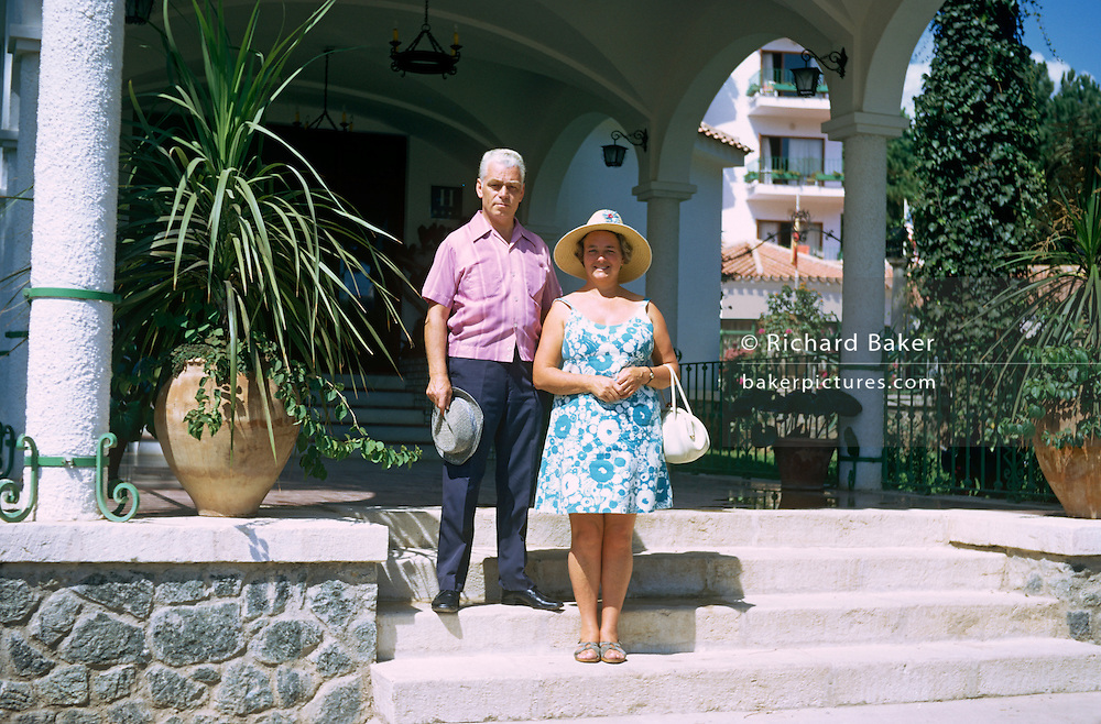 A middle-aged husband and wife stand on hotel steps in the Spanish Mediterranean resort of Marbella.