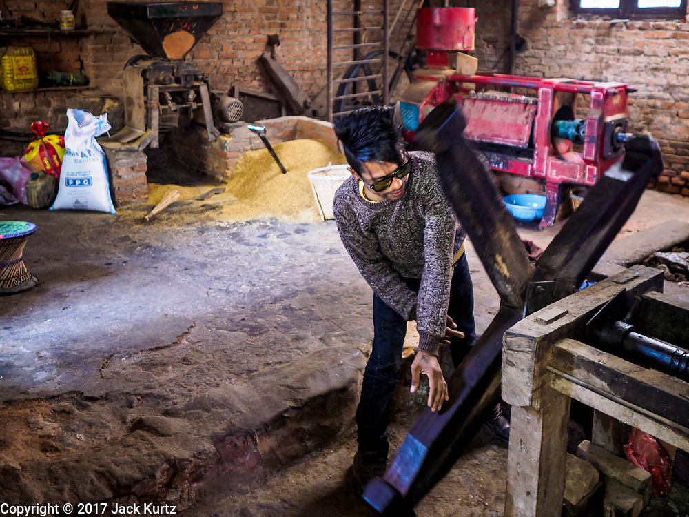 15 MARCH 2017 - KHOKANA, NEPAL: Workers make mustard oil at the Gaabu Jyaasha Oil Mill in Khokana, Nepal. The mustard oil is made by hand with local grown mustard seeds. The seeds are roasted then pressed in a large press operated by a hand screw. The first pressing of oil is sold in local markets around Khokana and shipped to grocery stores in Kathmandu. The seeds are pressed a second time in a mechanical press, and that oil is sold for use in oil massages. The dry remains are sold to local farmers for livestock and chicken feed or composting material. The mill is family owned and has been making mustard oil for seven generations. Mustard oil is used for cooking in North India, Eastern India, Nepal, Bangladesh and Pakistan. In Bengal, Orissa, Assam and Nepal, it is the traditionally preferred oil for cooking. It is illegal to import mustard oil into the US because of possible health issues with the oil.     PHOTO BY JACK KURTZ