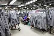A seamstress is surrounded by racks of dress shirts on a production floor at a Textile Alliance Apparel factory in Qingxi Township, Dongguan, Guangdong Province, China, on July 28, 2010. The factory supplies shirts and pants to major brands such as J Crew, Hugo Boss, Burberry, etc and produces over 300,000 shirts per day.