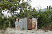 A young girl peeks from a store shack on the side of the road that leads up the mountain above Carrefour, Haiti after getting out of school.