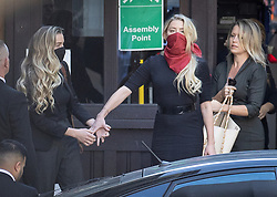 © Licensed to London News Pictures. 07/07/2020. London, UK. US actor Amber Heard (red facemask) reaches out to hold the hand of her sister Whitney Heard as she arrives at The High Court in Central London with Australian lawyer Jennifer Robinson (R). Johnny Depp's libel trial against The Sun newspaper is due to take place over the next three weeks over allegations he was violent and abusive towards his ex-wife Amber Heard. Photo credit: Peter Macdiarmid/LNP