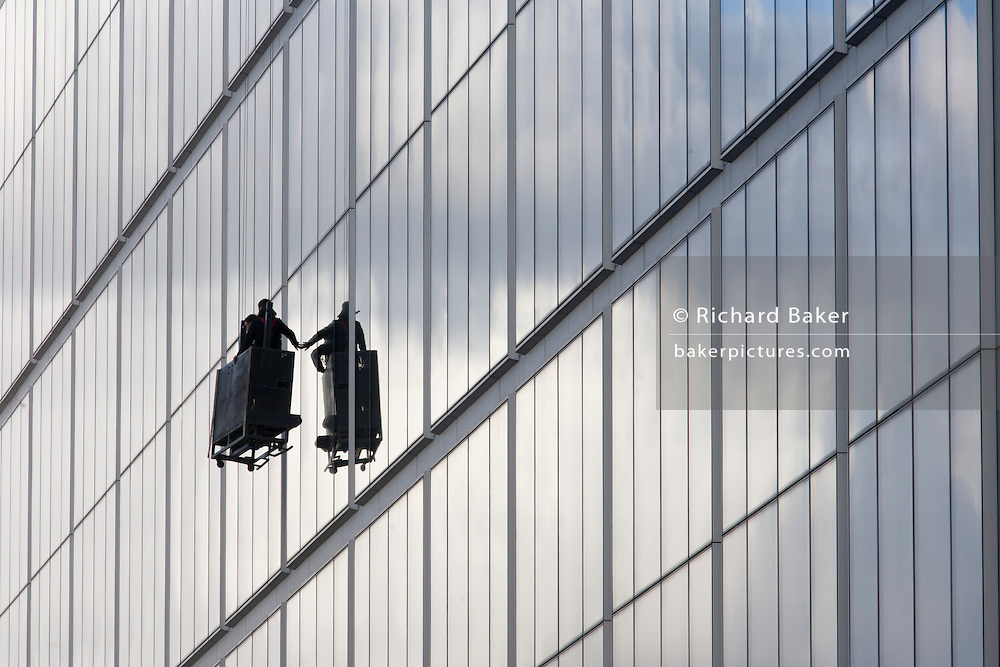 A team of two hang in mid-air, half-way down their contract cleaning operation to clear dirt and grime from a corporate office building in Spitalfields, London. One man touches the glass with his fingers as they travel back upwards to the top, before progressing along their route.