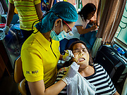 29 JANUARY 2018 - SANTO DOMINGO, ALBAY, PHILIPPINES: A woman who lives on Mayon volcano and has been evacuated to a shelter in Santo Domingo gets a dental exam in a mobile dental clinic visiting the shelter. Mayon volcano's eruptions continued Monday. At last count, more 80,000 people have been evacuated from their homes of the slopes of the volcano and are crowded into shelters in communities outside of the danger zone.    PHOTO BY JACK KURTZ