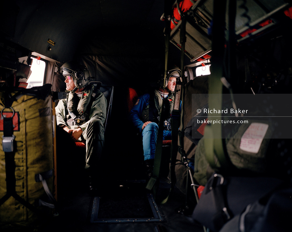 Members of the Red Arrows, Britain's RAF aerobatic team gaze out of respective windows during helicopter ride.