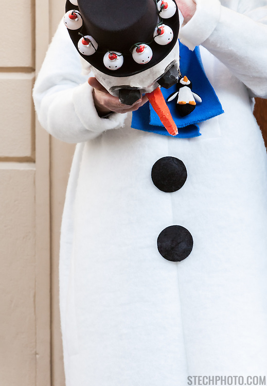 A man taking off the head and mask of his snowman costume while on a break in activities during carnival (Fastnacht) in Basel, Switzerland.