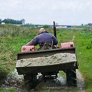 Nederland Delft 17-09-2010 20100917     A4 Delft - Schiedam wordt definitief verlengd,  er  is begin deze maand officieel besloten tot de aanleg van het stuk snelweg waarover zo'n vijftig jaar is gesproken. Natuurgebied dat in de toekomst zal moeten wijken na het doortrekken van de A4. Boer op traktor. Rijkswaterstaat en het ministerie van VWS hebben dat laten weten.Over de nieuwe verkeersader wordt al decennialang gesteggeld, vooral omdat de weg het natuurgebied Midden-Delfland doorboort...De zeven kilometer asfalt tussen Delft en Schiedam doorkruist straks verdiept of via een tunnel het natuurgebied tussen de twee steden. Het belangrijkste pluspunt is dat de A13 wordt ontlast. Op rijksweg A13 staat dagelijks de voor de economie schadelijkste file van Nederland. Met het project A4 Delft-Schiedam willen lokale en regionale overheden en het Rijk de problemen rond bereikbaarheid en leefbaarheid op en rond de A13 en de A4 Delft-Schiedam oplossen. Midden Delftland.