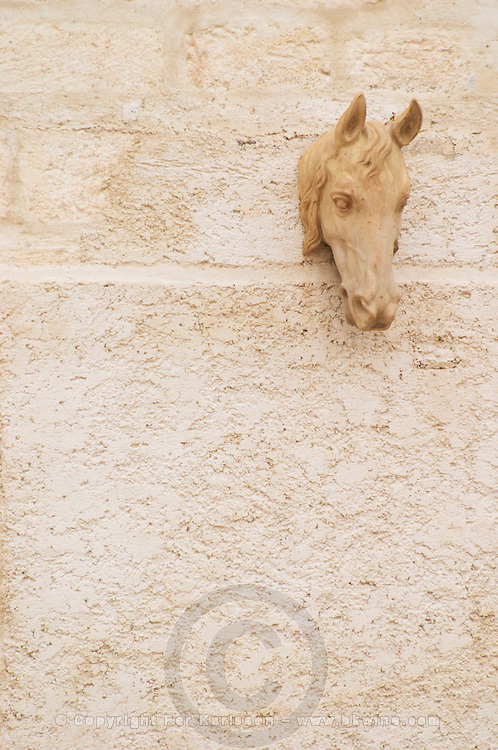 Chateau de Montpezat. Pezenas region. Languedoc. A statue of a horse's head hanging on the wall. France. Europe.