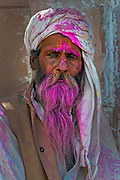 Portrait of Barsana man. The gang of men from Barsana arrive to raid the Temple of Shriji, during Lathmar Holi. Men from Barsana raid the town whilst being assaulted with coloured water sprayed from rooftops, they are beaten by Nandgaon's women with large sticks and smeared with Holi coloured powders in a counterpart festival to the one held in Barsana on the previous day. The spectacle is a riot of colour amidst frenzied celebrations.
