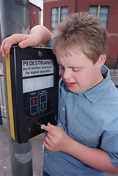 Teenage boy with Downs Syndrome pushing button at pedestrian crossing,