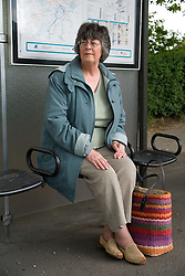 Woman sitting at a  bus stop waiting for a bus,