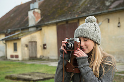 Teenage girl clicking pictures with retro styled camera, Munich, Bavaria, Germany