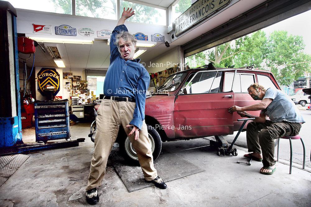 Nederland, Amsterdam , 3 juni 2014.<br /> Theatergroep Flint speelt Garagepoes.<br /> Tussen prachtige old-timers, afgewerkte oliedrums en autowrakken werkt een automonteur zich in het <br /> zweet, vlijt een pin-up zich uitdagend over de motorkap en dringt zich regelmatig een verstikkende moeder <br /> op. Garagepoes is een rauwe muziektheatervoorstelling die zich afspeelt in een autogarage. <br /> Op de foto: Felix Strategier (links) en Garagehouder Johan Kuin.<br /> <br /> Foto:Jean-Pierre Jans