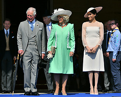 The Prince of Wales, the Duchess of Cornwall and the Duchess of Sussex, listen as the Duke of Sussex (not in view) speaks during a garden party at Buckingham Palace in London, which the newly weds are attending as their first royal engagement as a married couple.