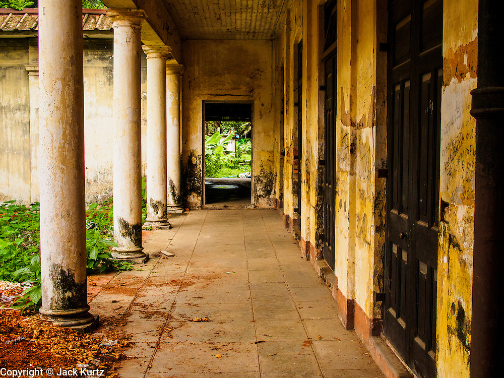 07 JUNE 2014 - YANGON, MYANMAR: A hallway at the Pegu Club. The Pegu Club in Yangon was the Officers' Club for the British Army when Myanmar was the British colony of Burma. The club, principally made of teak, is now abandoned and in decay. Squaters have moved into the parts of the complex still standing. Yangon has the highest concentration of colonial style buildings still standing in Asia. Efforts are being made to preserve the buildings but many are in poor condition and not salvageable.    PHOTO BY JACK KURTZ