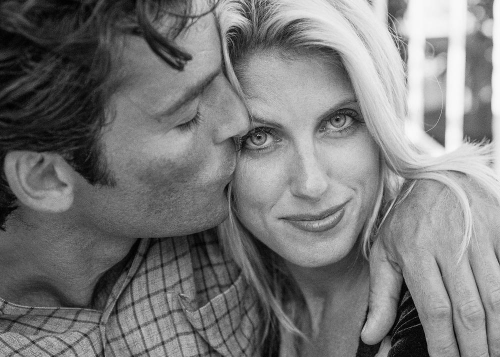 A Man kissing woman on the cheek.