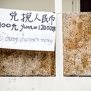 A sign for non-official currency exchange from Chinese yuan to Lao kip in Luang Prabang, Laos.