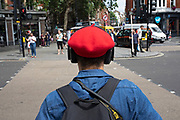 Rear view of a man wearing a  red beret, headphones and a backpack in London, United Kingdom.