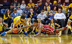 Feb 2, 2019; Morgantown, WV, USA; Oklahoma Sooners forward Kristian Doolittle (21) dives for a loose ball while West Virginia Mountaineers guard Jermaine Haley (10) picks the ball up during the second half at WVU Coliseum. Mandatory Credit: Ben Queen-USA TODAY Sports