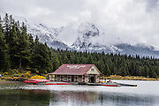 Cloudy, snow-dusted peaks of the Queen Elizabeth Ranges rise over Maligne Lake Boat House in mid September, in Jasper National Park, Canadian Rockies, Alberta, Canada. Jasper is the largest national park in the Canadian Rocky Mountain Parks World Heritage Site declared by UNESCO in 1984.