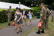 Young girls walk past soldiers from the Coldstream Guards (from nearby Windsor barracks and deploying to Afghanistan later this year) after a day's racing during the annual Royal Ascot horseracing festival in Berkshire, England. Royal Ascot is one of Europe's most famous race meetings, and dates back to 1711. Queen Elizabeth and various members of the British Royal Family attend. Held every June, it's one of the main dates on the English sporting calendar and summer social season. Over 300,000 people make the annual visit to Berkshire during Royal Ascot week, making this Europe's best-attended race meeting with over £3m prize money to be won.