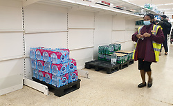 © Licensed to London News Pictures. 30/07/2021. London, UK. A Sainsbury's staff member wearing a face covering walks past nearly-empty shelves of bottled drink water in Sainsbury's, north London. Record breaking numbers of people have been forced to self-isolate after being alerted by the NHS Covid-19 app. The pingdemic has seen staff shortages at supermarkets, resulting in less stock making its way to supermarket shelves. Labour leader Sir Keir Starmer has demanded that the government brings forward the end to self-isolation from 16 August to 7 August. Photo credit: Dinendra Haria/LNP