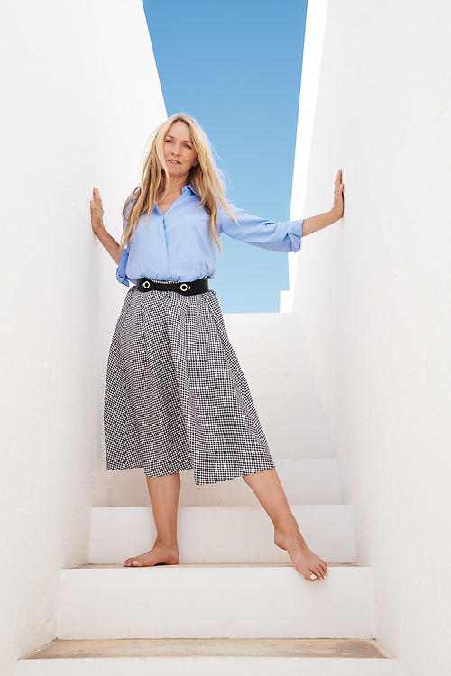 Collette Dinnigan, posing on a staircase at Masseria Moroseta. Ostuni, Italia. September 28, 2019.